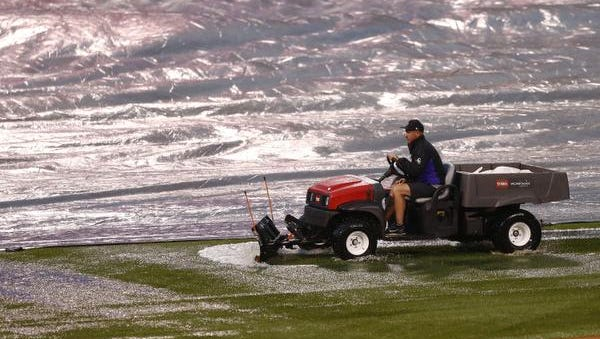 A member of the Coors Field grounds crew pushes standing water off the field during a delayed baseball game between the Chicago Cubs and Colorado Rockies, Monday, May 8, 2017, in Denver. (AP Photo/ Jack Dempsey)