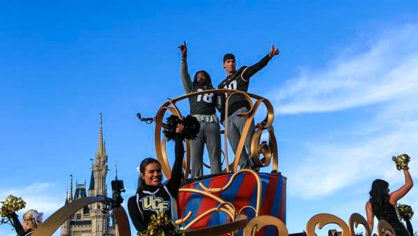 Central Florida football players Shaquem Griffin, left, and McKenzie Milton wave to fans during the a parade at Walt Disney World in the Magic Kingdom on Sunday, Jan. 7, 2018, in Orlando, Fla. (Jacob Langston/Orlando Sentinel via AP)