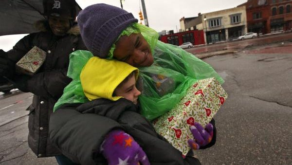 Robert Tucker, 50, holds a gift as Kim Alegers, 47, gives Caleb White, 11, a hug after receiving a gift box from him on Trumbull and Michigan Ave.