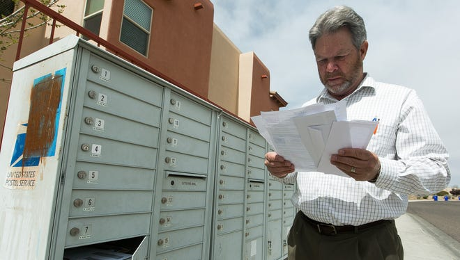 Bruce Ball, of Las Cruces, looks over his medical bills near his mailbox on Tuesday, March 8, 2016. Ball recently experienced a surprise medical bill after a visit to the Emergency Room at Memorial Medical Center, which is in his insurance plan's network. He received two bills: one from the hospital and another from the physician, which he was not expecting to receive.