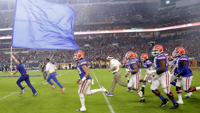 Florida coach Dan Mullen, center, runs onto the field for the Orange Bowl game against Virginia on Dec. 30, 2019, in Miami Gardens.
