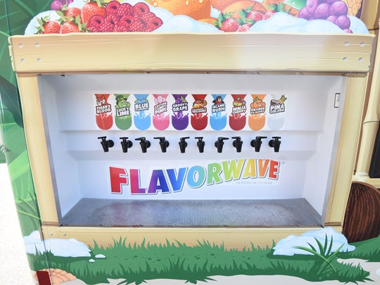 Customers pour flavoring over shaved ice at the Flavorwave station on the Kona Ice food truck.
