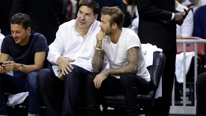 Former soccer player David Beckham, of England, right, sits with Bolivian businessman Marcelo Claure, during Game 1 of an Eastern Conference semifinal basketball game between the Miami Heat and Brooklyn Nets, Tuesday, May 6, 2014, in Miami.
