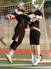 Appoquinimink's Jackson Truitt (left) celebrates with Cross Ferrara after a goal by Ferrara in the fourth quarter of Appoquinimink's 12-8 win against Tower Hill in a semifinal of the DIAA state tournament Wednesday at Caravel Academy.