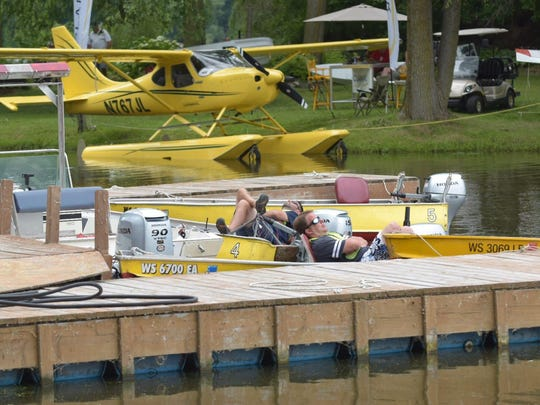 A pair of EAA volunteers wait to park aircraft in the lagoon at the Oshkosh Seaplane Base in Willow Harbor.