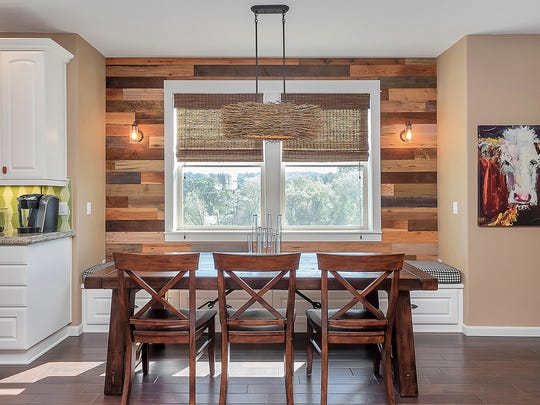 Meagher's dining room now features reclaimed barn-wood accent walls and layered lighting, including Edison-style fixtures on the barn wood.