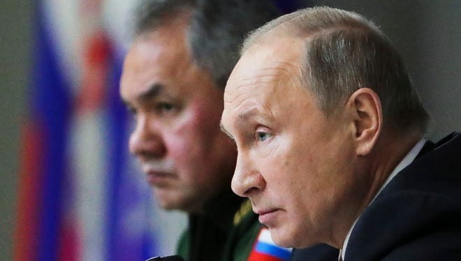 Russian President Vladimir Putin, seated next to Defense Minister Sergei Shoigu at a defense meeting in Balashikha, outside Moscow, Dec. 22, 2017. accuses the U.S. of violating a landmark Cold War-era arms nuclear pact.
