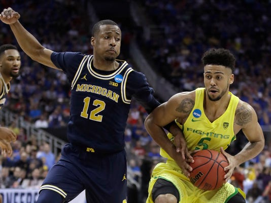 Oregon guard Tyler Dorsey drives past Michigan guard Muhammad-Ali Abdur-Rahkman (12) during the second half of a regional semifinal of the NCAA men's college basketball tournament, Thursday, March 23, 2017, in Kansas City, Mo. Oregon won 69-68. (AP Photo/Charlie Riedel)