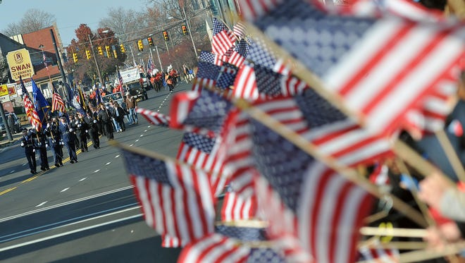 A sea of flags greets the start of the 2015 Veterans Day Parade in downtown Mansfield. This year's parade will step off Saturday morning.
