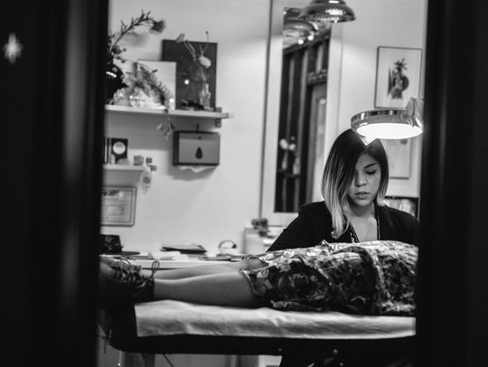 Hand-poke tattoo artist Taylor Elyse Compton completes