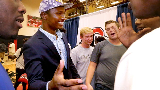 Oakland football player JaCoby Stevens, celebrates with his teammates after announcing that is committed to LSU on Monday, Aug. 8, 2016.