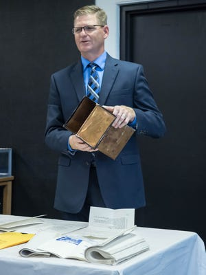 Harper Creek Superintendent Rob Ridgeway holds the copper time capsule removed from the recently demolished Wattles Park Junior High School on Crosby Drive.