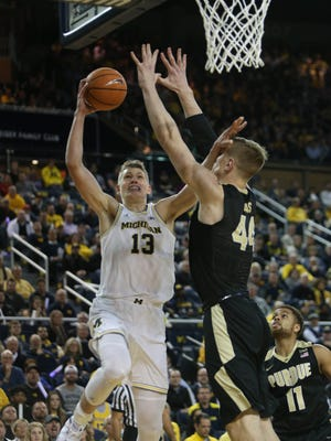 Michigan forward Moritz Wagner scores against Purdue center Isaac Hass during the first half on Tuesday, Jan. 9, 2018, at Crisler Center.