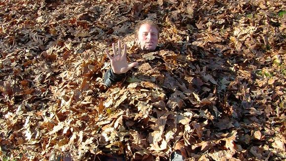 Josh Farley buried under leaves.