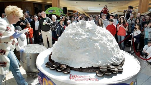 FILE - In this Saturday, March 26, 2011 file photo, Amy Bouchard, owner of Wicked Whoopies, far left, puts the final dollops of filling on an over-1000-pound Whoopie Pie before adding the top devil's food layer at the Maine Mall in South Portland, Maine. Maine's legislature voted in favor of making the Whoopie Pie the state snack. When New Hampshire lawmakers this month shot down as frivolous a group of fourth-graders' effort to name the red-tailed hawk the official state raptor, the pols got pasted as insensitive bullies. But in a state with an official tree, bird, dog, animal, insect, amphibian, butterfly, saltwater fish, freshwater fish, rock, mineral, gem and, yes, tartan, some say the legislators have a point.