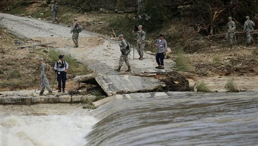 Members of the National Guard and a search and rescue team work along the Blanco River, Tuesday, May 26, 2015, in Wimberley, Texas. Authorities say recovery teams continue to search for as many as a dozen missing people in an area where punishing rains have destroyed or damaged more than 1,000 homes and killed at least three people statewide this past weekend. (AP Photo/Eric Gay)