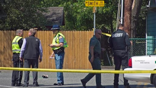 Police stand near the scene where a vehicle hit a group of students who were walking on a sidewalk as part of a school physical education exercise, Wednesday, June 10, 2015, near Bellingham, Wash. Two of the students were killed, and Washington State Trooper Mark Francis said the driver of the vehicle was arrested for investigation of vehicular homicide and vehicular assault. (Philip Dwyer/The Bellingham Herald via AP)