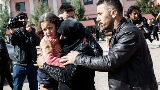 A Turkish man helps a Syrian woman carrying a wounded Syrian girl to a hospital in Kilis, Turkey, Monday, Feb. 15, 2016. An airstrike in the northern Syrian province of Idlib destroyed a makeshift clinic supported by an international aid group on Monday, killing and wounding several people, activists and the group said. Doctors Without Borders, also known by its French acronym MSF, said in a statement that the hospital was hit with four times in two series of at least two attacks. It said the attacks were minutes apart adding that at least eight members of staff are currently missing. (AP Photo/Halit Onur Sandal)