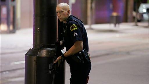 Un policía de Dallas monta guardia en una calle en el centro de Dallas, el jueves 7 de julio de 2016, tras noticias sobre disparos durante una protesta por la muerte de dos hombres negros por disparos de la policía en Louisiana y Minnesota. (AP Foto/LM Otero)