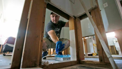 In this Thursday, Nov. 3, 2016 photo, Jason Meier paints flood damaged wall studs in his flood damaged home in Virginia Beach, Va. Hundreds of homes in the area were damaged from floodwaters from the remnants of Hurricane Matthew.