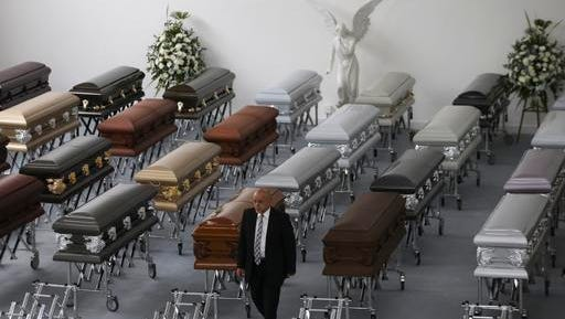 A funeral employee walks past coffins containing the remains of the victims of the Colombian air tragedy are lined up in the parking garage of the San Vicente funeral home in Medellin, Colombia, Thursday, Dec. 1, 2016. Because of the large number of casualties, the funeral home had to place the coffins in its parking garage. Forensic authorities say they have managed to identify a majority of the victims of Monday's crash and hope to finish their work on Thursday.