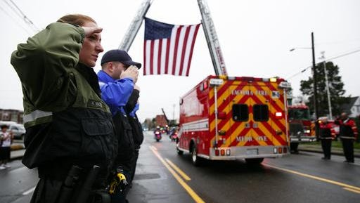 """Tacoma Police Department animal control officer Kate Madden salutes during the procession for Tacoma police Officer Reginald """"Jake"""" Gutierrez on Friday, Dec. 2, 2016 in Tacoma, Wash. Crowds gathered to pay respects to Gutierrez who died Wednesday after being shot while responding to a domestic violence call."""