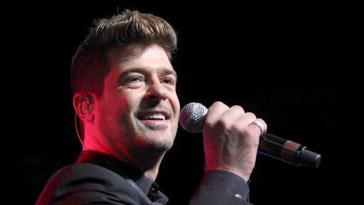 FILE - In this Aug. 7, 2015 file photo, Robin Thicke performs during the Steve Harvey Morning Show live broadcast at the Georgia World Congress Center in Atlanta. A judge has ordered Thicke to stay away from his ex-wife, actress Paula Patton and only have monitored visits with his 6-year-old son. Los Angeles Superior Court Judge Colin Leis issued the temporary restraining order on Thursday, Jan. 26, 2017, after Patton accused the singer of physically abusing her during their marriage, which ended in March 2015.