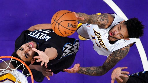 Los Angeles Lakers forward Brandon Ingram, right, shoots as Minnesota Timberwolves center Karl-Anthony Towns defends during the first half of an NBA basketball game, Sunday, April 9  in Los Angeles.