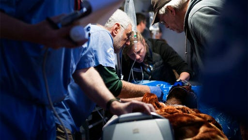 In this March 23, 2017 photo, American medical volunteers attend to a civilian casualty of the battle to retake Mosul from Islamic State militants, at the the Samaritan's Purse field hospital, in Bartella, Iraq. Situated on the outskirts of Mosul, the state-of-the-art field clinic was set up last December by Samaritan's Purse, a Christian aid organization based in Boone, North Carolina. Its volunteer doctors receive those with the gravest injuries from the field clinics inside or at the very edge of Mosul, where casualties are initially treated.