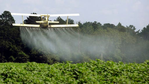In this photo taken Aug. 4, 2009 file photo, a crop duster sprays a field of crops just outside Headland, Ala. Dow Chemical is pushing the Trump administration to scrap the findings of federal scientists who point to a family of widely used pesticides as harmful to about 1,800 critically threatened or endangered species.