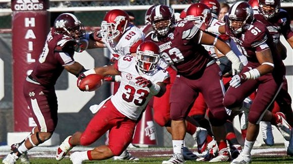 Arkansas running back Dennis Johnson (33) runs away from Mississippi State defensive linemen P.J. Jones (93) and Preston Smith (91) in the third quarter of an NCAA college football game in Starkville, Miss., Saturday, Nov. 17, 2012.  Mississippi State won 45-14. (AP Photo/Rogelio V. Solis)