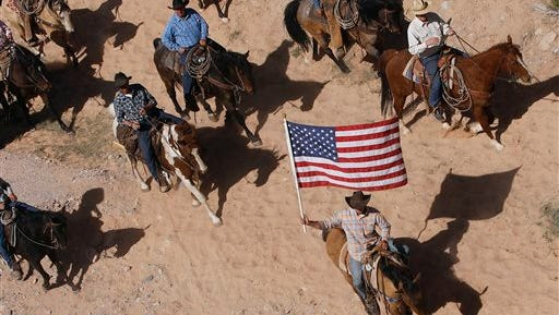 FILE - In this April 12, 2014, file photo, the Bundy family and their supporters fly the American flag as their cattle is released by the Bureau of Land Management back onto public land outside of Bunkerville, Nev.