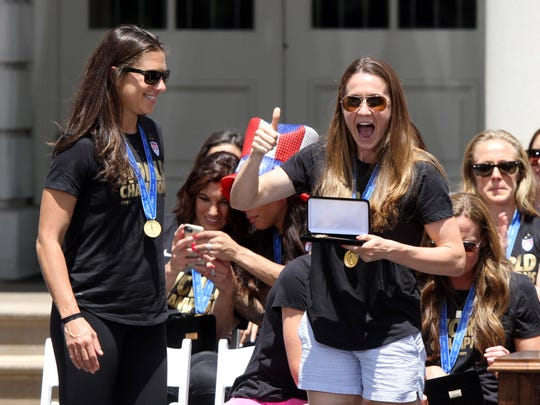 Women's FIFA World Cup Championship team member Heather O'Reilly gives a thumbs up after getting the key to New York City during a ceremony outside City Hall in New York City Friday, July 10, 2015. Carli Lloyd heads up to get her key too.