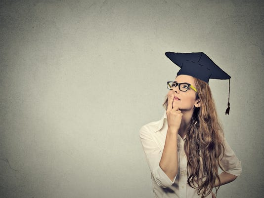 graduate student woman in cap gown looking up thinking