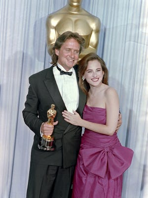 "Michael Douglas, accompanied by actress Marlee Matlin poses with his Osars of best actor for the film ""Wall Street"" during the 60th Annual Academy Awards, on April 11, 1988."