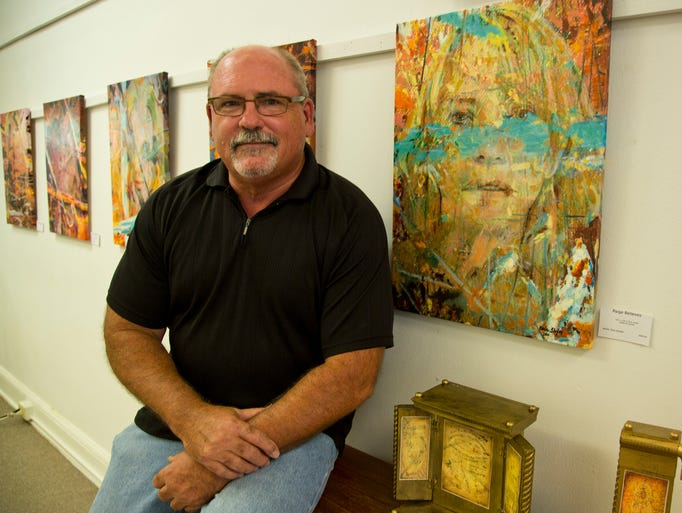 "Local artist and writer Orie Shafer with his oil and mixed media on canvas piece titled ""Paige Believes""  at his exhibit at Something Special of Lafayette Art Gallery Tuesday, July 22, 2014, in Lafayette. Shafer is debuting a three-part show, first time he has exhibited locally for years. The first is a response to his wife's experience with chronic illness, the second is a parody on what is art and how it's framed, the third is an homage to Leonardo da Vinci."