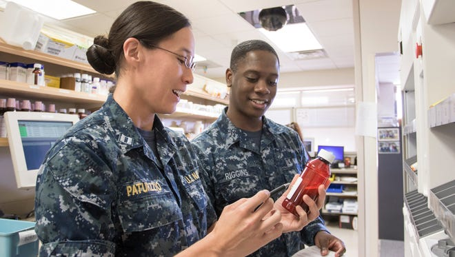 Lt. Mindy Paturzzio, left, talks about a medication Sept. 22, 2016, with Darius Riggins, a pharmacy technician, at Pensacola Naval Hospital.