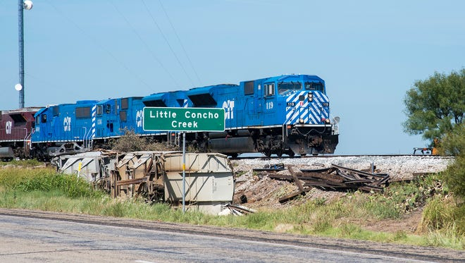 The first train to venture over the repaired tracks inches its way through the site of a derailment of several cars carrying frac sand east of Miles Thursday, August 10, 2017.