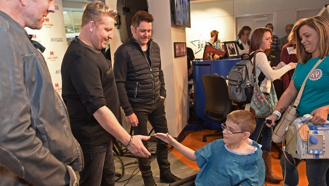 Kaiden Bouland shakes hands and gets his photo made with members of Rascal Flatts as they visited Monroe Carell Jr. Children's Hospital at Vanderbilt on Nov. 7, 2016, for a special performance at the Seacrest Studios for the patients.