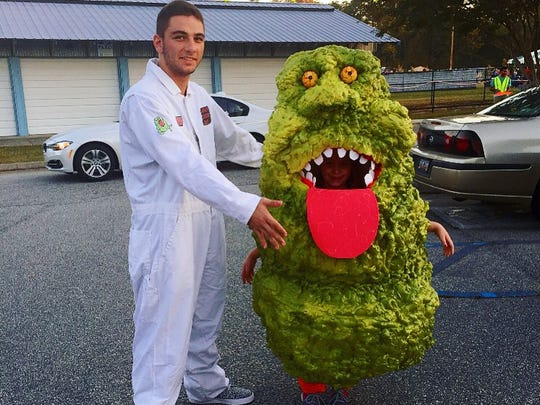 Chamberlyn Livingston, 6, wears a slimer costume alongside big brother Tyelen Gray, 16, as a ghostbuster.