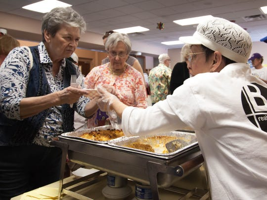 Volunteer Marianne Rosenthan, right, serves kugel to Marleme Lavetts, left, and Nancy Jenkins during a previous Jewish Food and Folk Festival at Temple Beth-El.