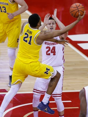 Michigan's Zak Irvin shoots against Wisconsin's Bronson Koenig during the first half Tuesday, Jan. 17, 2017 in Madison, Wis.