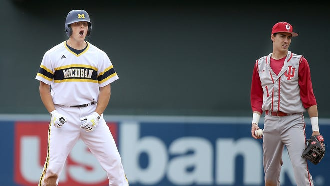 Michigan's Carmen Benedetti, left, celebrates his RBI double in the sixth inning during the Big Ten baseball tournament at Target Field on Wednesday, May 20, 2015, in Minneapolis.