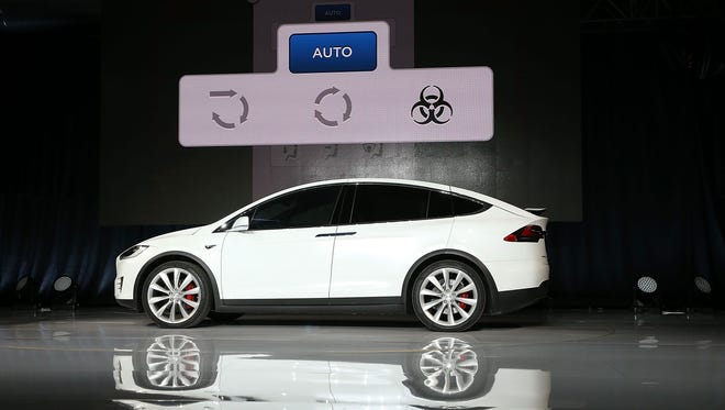 "One of the new Tesla Model X crossover SUV's features will be bio weapon defense mode,"" as denoted by the actuual button symbol displayed above"