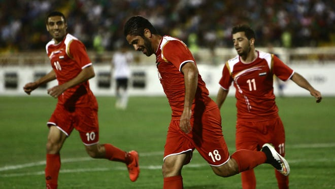 Abdulrazak al-Husein (L), Raja Rafe (C) and Mahmoud Almawas (R) of Syria celebrate after scoring a goal during their 2018 World Cup qualifying group E football match against Afghanistan at Samen stadium in Iran's northeastern city of Mashhad on June 11, 2015.