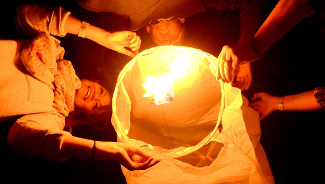 A group of attendees light a lantern at a previous festival in Fernley.