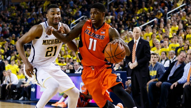 Dec 30, 2014; Ann Arbor, MI, USA; Illinois Fighting Illini guard Aaron Cosby (11) moves the ball while defended by Michigan Wolverines guard/forward Zak Irvin (21) in the second half at Crisler Center. Michigan won 73-65 in overtime. Mandatory Credit: Rick Osentoski-USA TODAY Sports