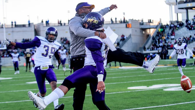 Prairie View coach Willie Simmons celebrates with Marquice O'Leary (32) after he intercepted the ball against Alabama State late in the second quarter on the ASU campus in Montgomery, Ala. on Saturday November 14, 2015. (Mickey Welsh / Montgomery Advertiser)