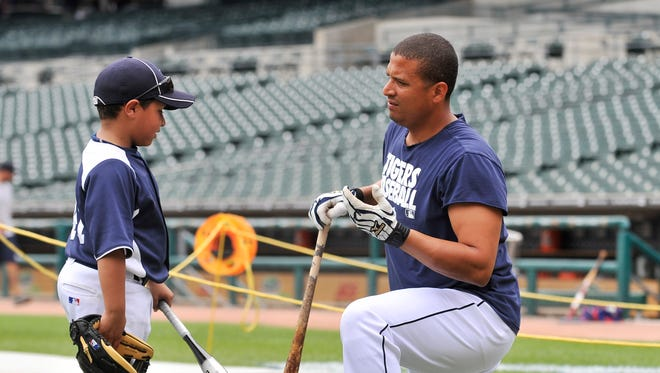 Victor Martinez talks to his son, Victor Jose Martinez, during batting practice before a game in 2011.