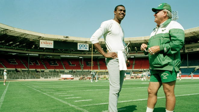 Eagles coach Buddy Ryan, right, talks with quarterback Randall Cunningham during a workout at London's Wembley Stadium in 1989,